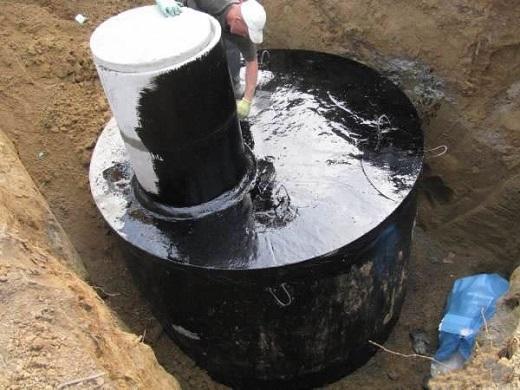 На фото показан процесс гидроизоляции септика из бетонных колец
