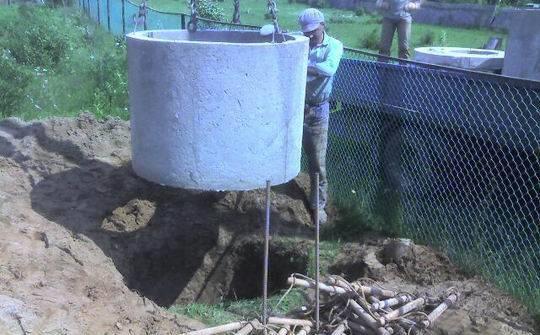 На фото показан процесс монтажа однокамерного септика из бетонных колец