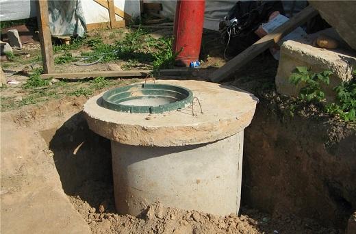 На снимке показан этап засыпки септика из бетонных колец